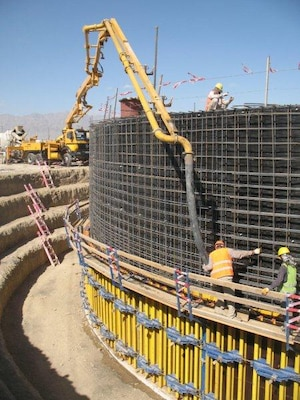 Workers use a boom concrete pump truck to place concrete around the metal shell of a Cut & Cover tank at Bagram Airfield, Afghanistan.  Each layer of concrete is allowed to set before additional concrete is placed, until the entire tank is protected by concrete.  (Photo by Clay Bolton)