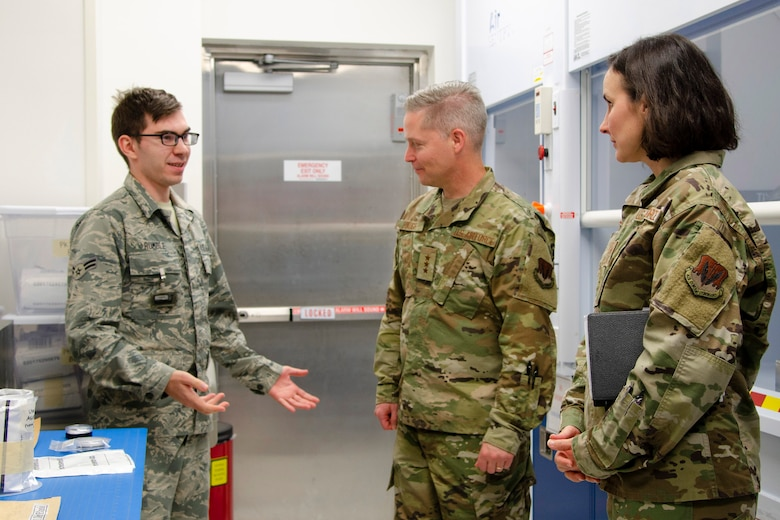 Airman 1st Class Ethan Rumble (left), a sample control technician at the Air Force Radiochemistry Laboratory, Patrick AFB, Fla., describes to 16th Air Force (Air Forces Cyber) Commander Lt. Gen. Timothy Haugh (center) and 16th AF Command Chief Master Sgt. Summer Leifer how he processes radiologic samples that arrive at the lab for analysis as part of the Air Force Technical Applications Center's nuclear treaty monitoring mission.  Haugh and Leifer traveled from San Antonio to get a glimpse into AFTAC's instrumental role in 16th AF's information and multi-domain operations. (U.S. Air Force photo by Susan A. Romano)