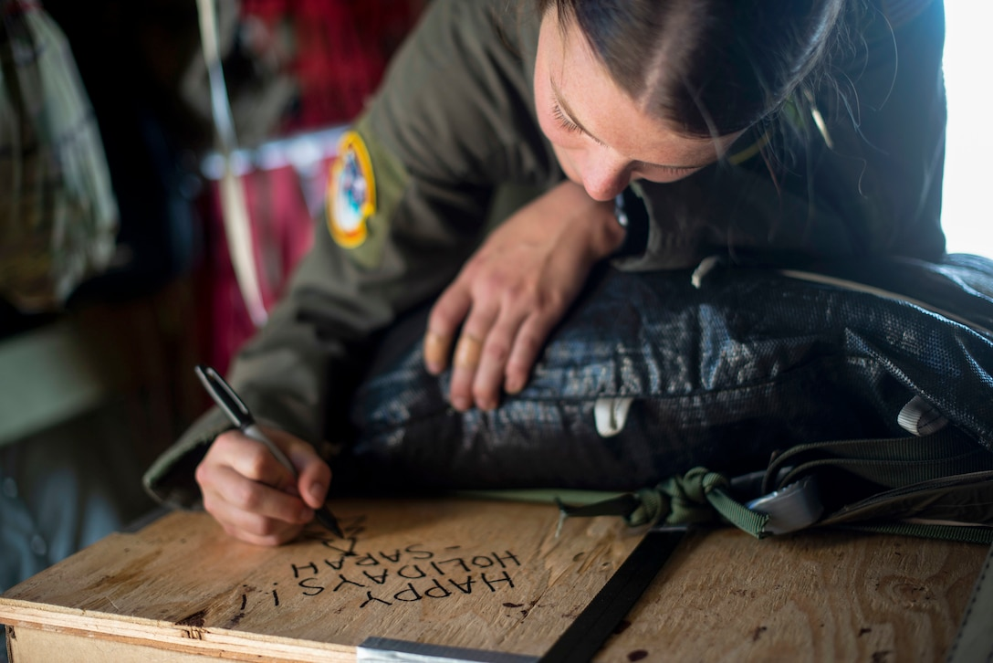 Airlift Squadron loadmaster, writes a holiday greeting on a box of humanitarian aid