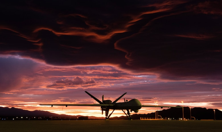 An MQ-9 Reaper sits on the flightline as the sun sets