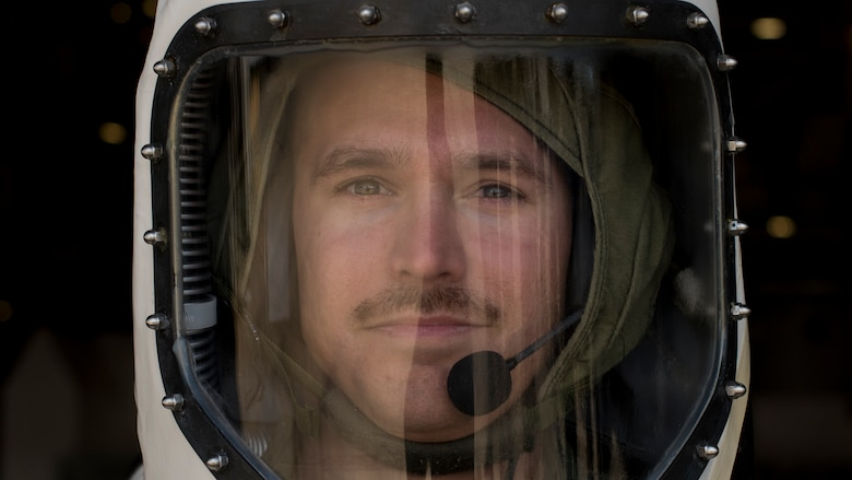 Technician stands in a Self-Contained Atmospheric Protective Ensemble suit