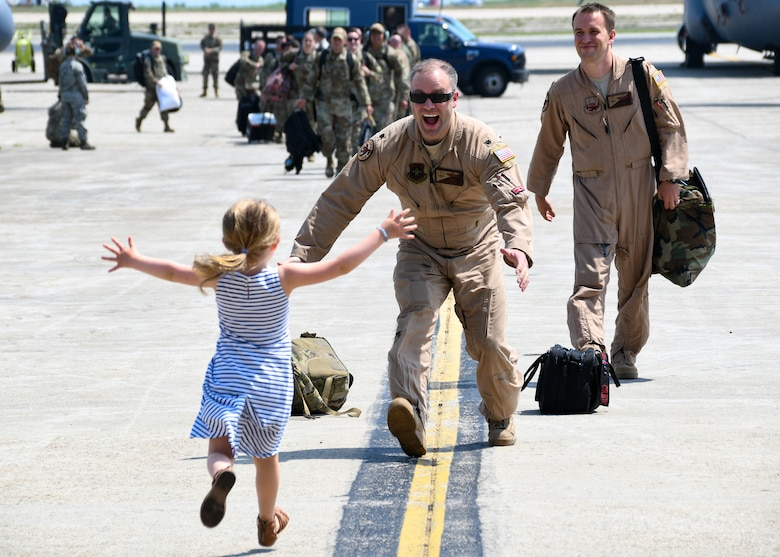 An Airman reunites with a family member as he returns home from their recent deployment
