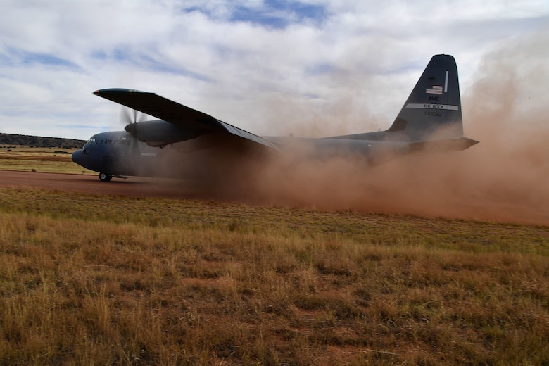 A C-130J Hercules prepares to take off from a dirt runway