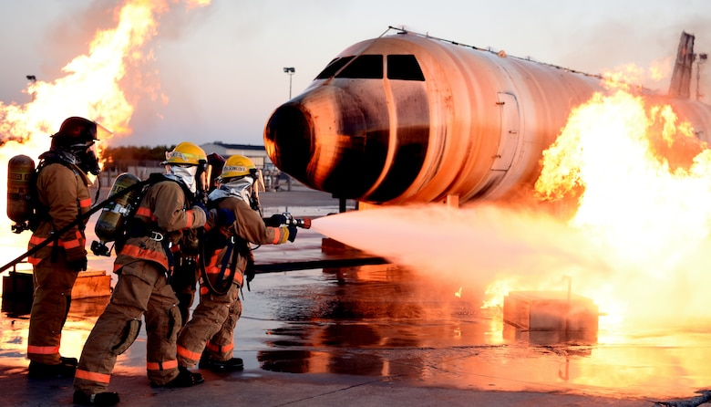 Airman approaches an exterior aircraft fire with a water hose during training
