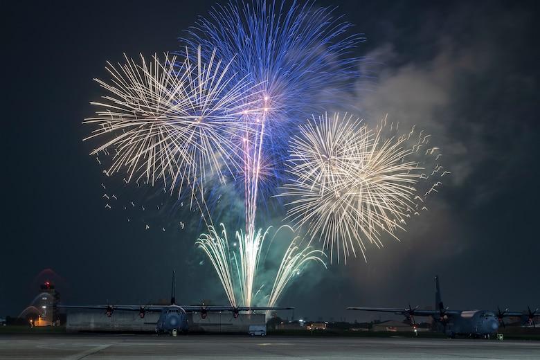 Fireworks explode behind a C-130J Super Hercules