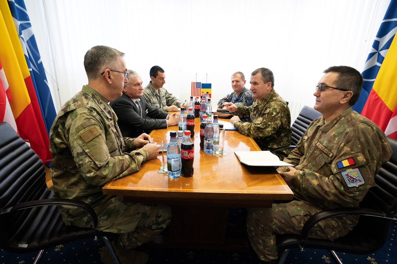 A group of military officers sit around a table.