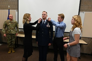 Photo of promotion rank of colonel being placed on service dress jacket of Col. Jon Wahlgren.
