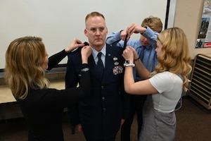 Photo of promotion rank of colonel being placed on the uniform of Col. Jon Wahlgren.