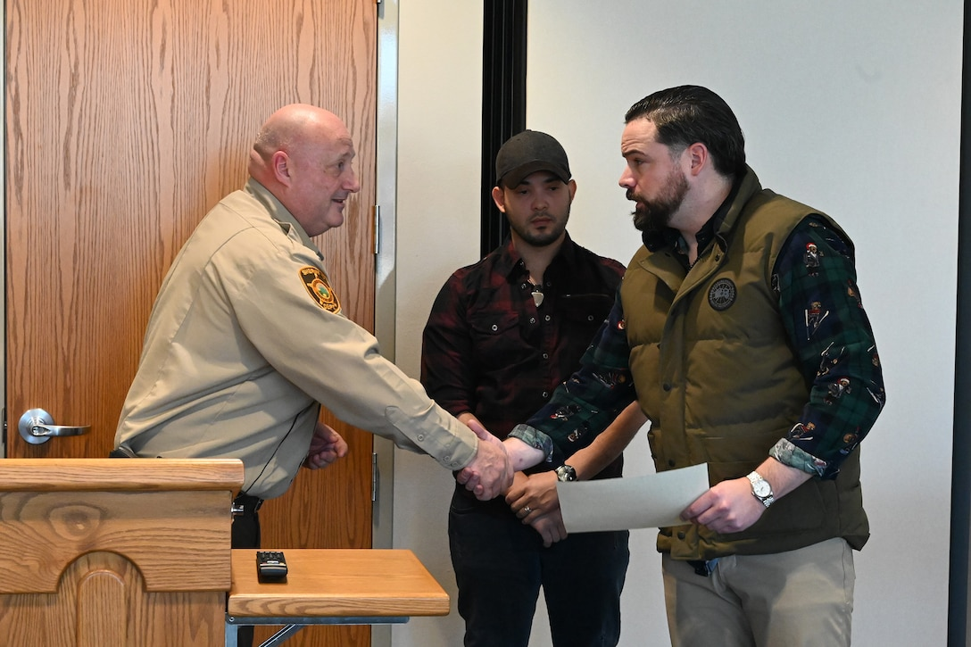 Photo of Ward County Sheriff Bob Roed congratulating Tech. Sgt. Ryan Fontaine and presenting certificate of courage.