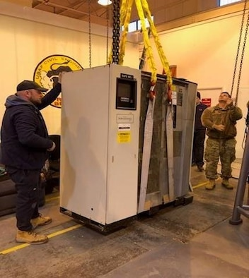 Airmen and civilian personnel from the 422nd Communications and Civil Engineer Squadrons, hoist a B31 Uninterruptable Power System on a pulley, Nov. 14, 2019, at RAF Croughton, England. The B31 UPS helps power the 422nd CS technical control facility that serves as one of the main hubs of communication across 5 MAJCOMS. (Courtesy Photo)