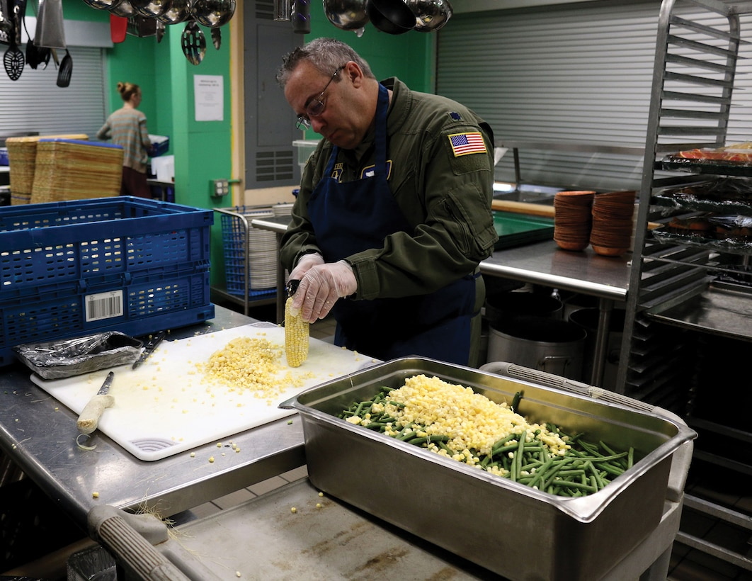 Lt. Col. Jerry Quincy, director of operations for the 89th Airlift Squadron, cuts corn off the cob while volunteering at the House of Bread in Dayton, Ohio Dec. 8, 2019. The House of Bread serves nearly 250 people a day. (U.S. Air Force photo/Staff Sgt. Joel McCullough)