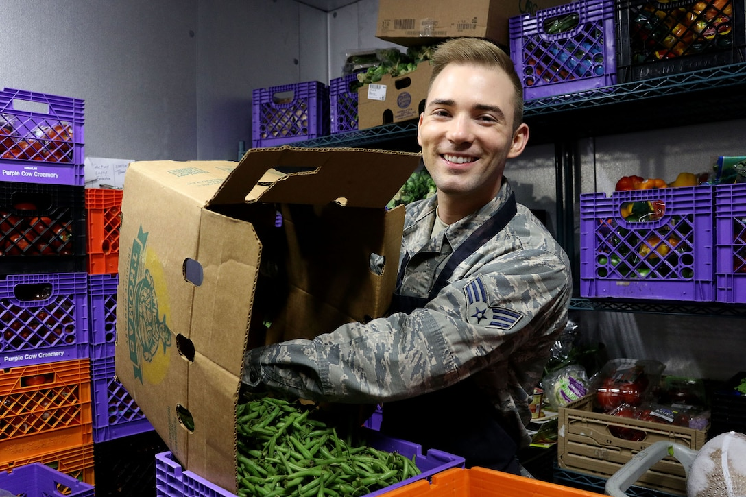 Senior Airman Gordon Sullivan, 89th Airlift Squadron commander's support staff, empties boxes of green beans in the walk in refrigerator at the House of Bread in Dayton, Ohio Dec. 8, 2019. The house receives donated food from stores in the local area, they then disseminate it to local people in need. (U.S. Air Force photo/Staff Sgt. Joel McCullough