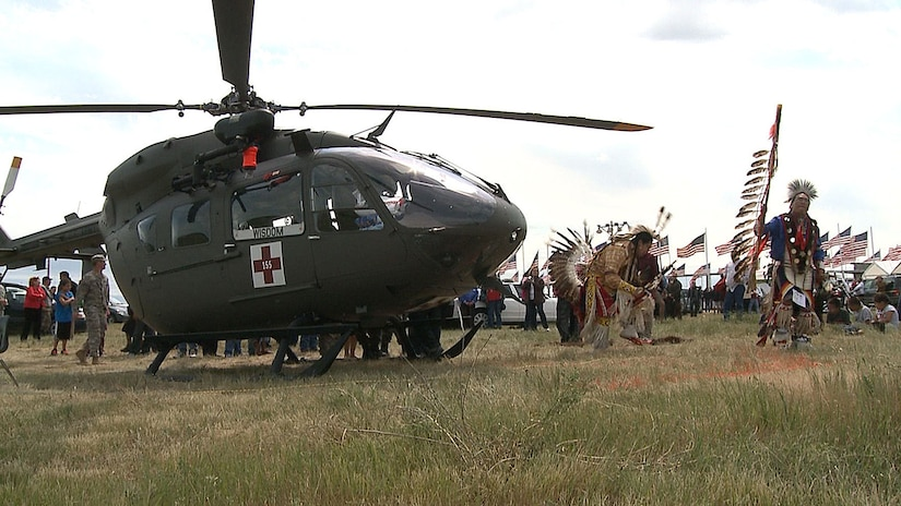 Two men dressed in Native American garb dance near a UH-72 Lakota helicopter in a field.