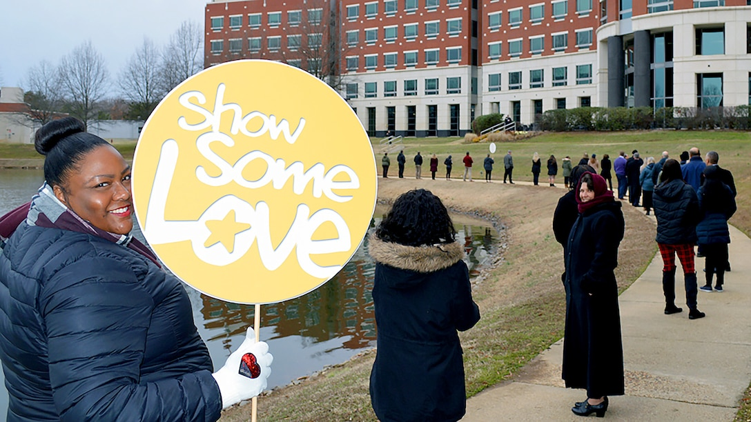 """Woman in blue coat holds up a """"Show Some Love"""" sign during an event at the McNamara Headquarters Complex pond at the agency's Fort Belvoir, Virginia, headquarters."""