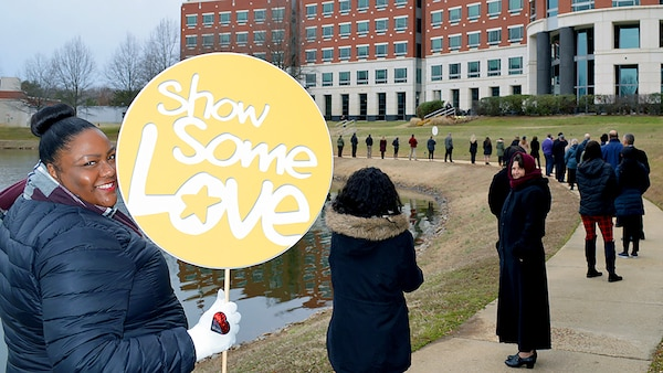 "Woman in blue coat holds up a ""Show Some Love"" sign during an event at the McNamara Headquarters Complex pond at the agency's Fort Belvoir, Virginia, headquarters."