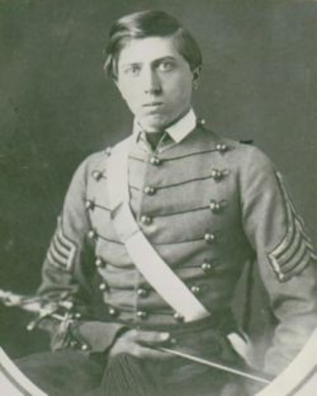 A young Civil War soldier in dress uniform looks at the camera as he holds a sword across his body