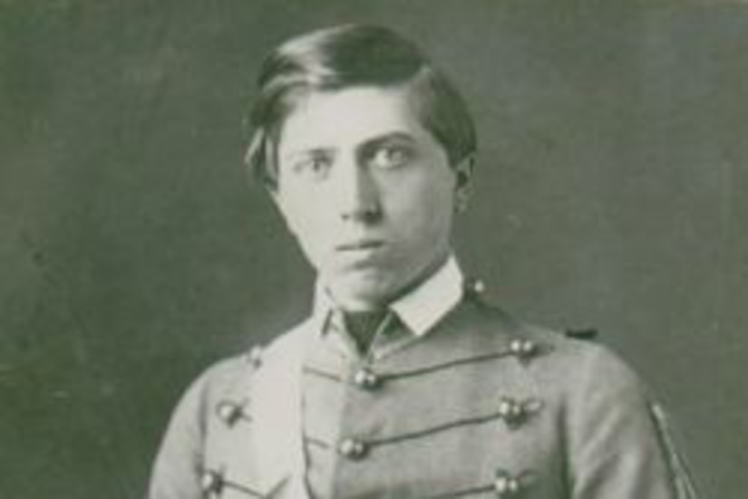 A young Civil War soldier in dress uniform looks at the camera as he holds a sword across his body.