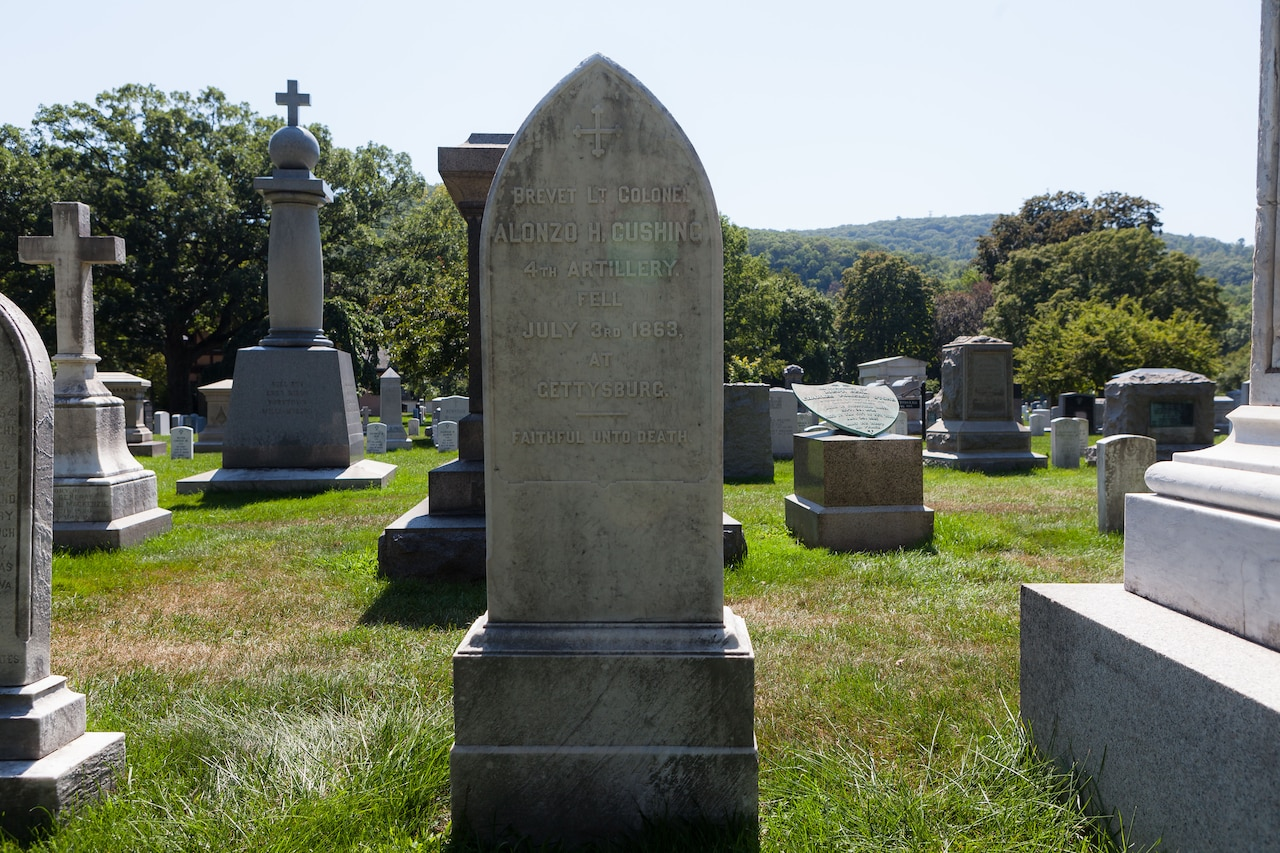 "A large headstone in a graveyard reads ""Brevet Lt. Colonel Alonzo H. Cushing."" Other headstones are spaced out around it."