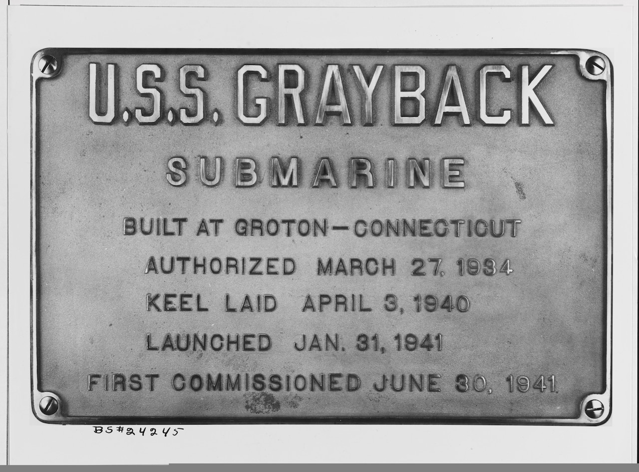 """A plaque reads """"USS Grayback,"""" amid other descriptions of its launching details."""