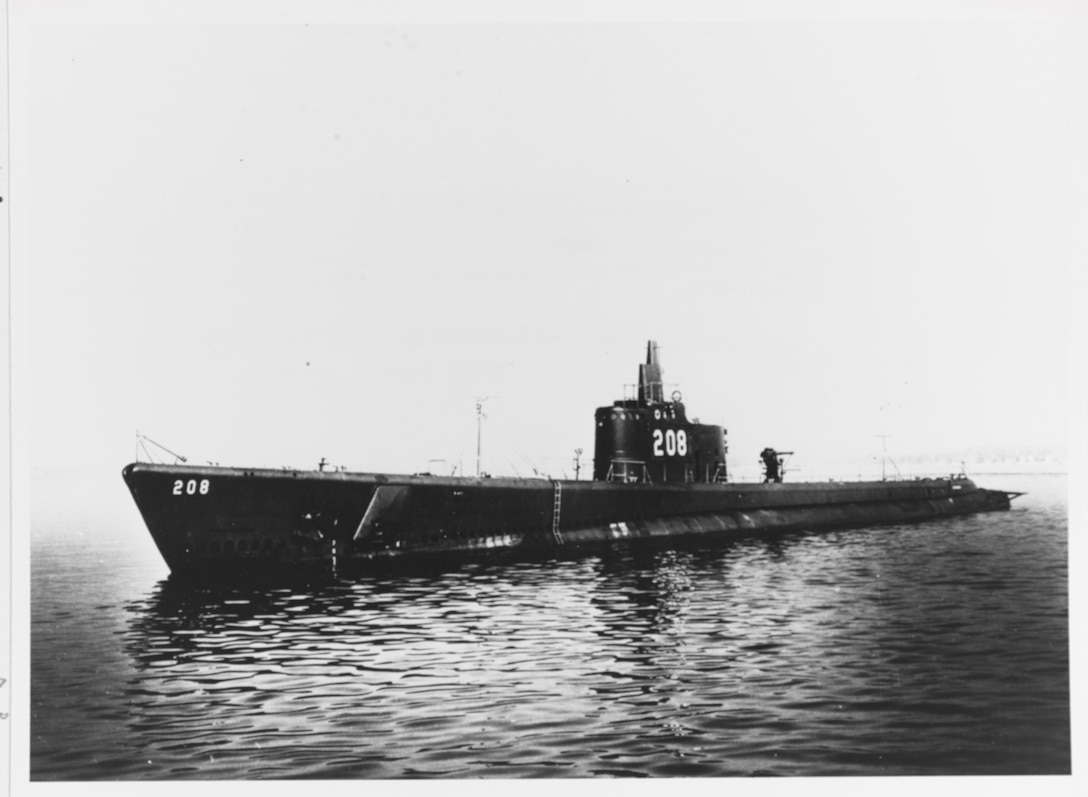 A 1940's era submarine glides across water.