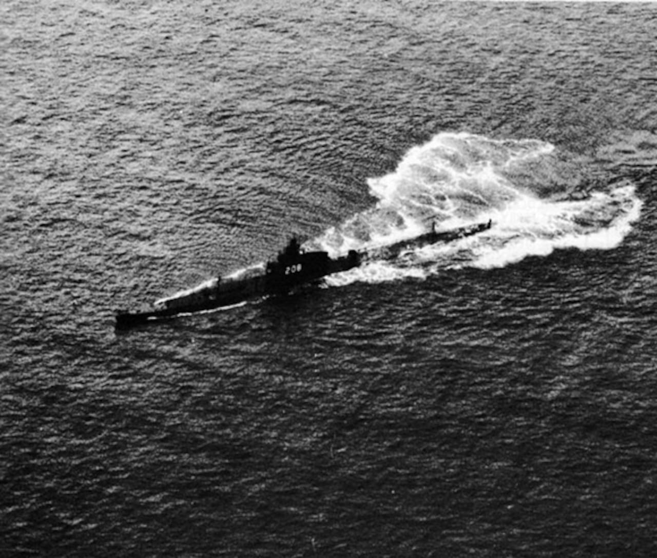 A 1940's era submarine chugs along above water.