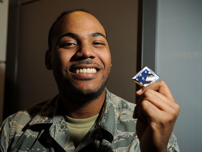 Airman 1st Class Bendali Eugene, Communications Information Group knowledge manager, is presented with the Diamond Sharp Award by First Sgts Senior Master Sgt. William Schipper and Master Sgt. Juan Villa at the National Air and Space Intelligence Center on Wright-Patterson Air Force Base, Ohio, Dec. 18, 2019. The Diamond Sharp Award recognizes Airmen who have actively demonstrated their commitment to Air Force values or have gone above and beyond in helping others. (U.S. Air Force photos by Staff Sgt. Seth Stang)