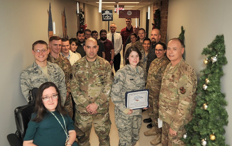 Staff Sgt. Mikayla Dlask, Future Threats Analysis Squadron force modernization analyst, is presented with the Diamond Sharp Award by First Sgts Senior Master Sgt. William Schipper and Juan Villa at the National Air and Space Intelligence Center on Wright-Patterson Air Force Base, Ohio, Dec. 18, 2019. The Diamond Sharp Award recognizes Airmen who have actively demonstrated their commitment to Air Force values or have gone above and beyond in helping others. (U.S. Air Force photos by Staff Sgt. Seth Stang)