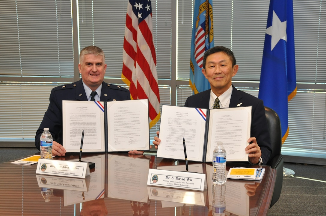 Two men sit holding documents.