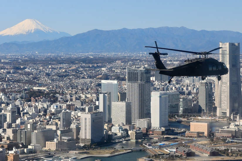 A military helicopter flies above a city in Japan.