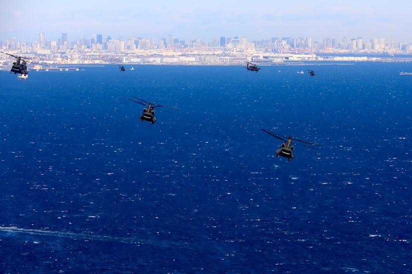 A group of military helicopters fly above the water with a coastline behind them.
