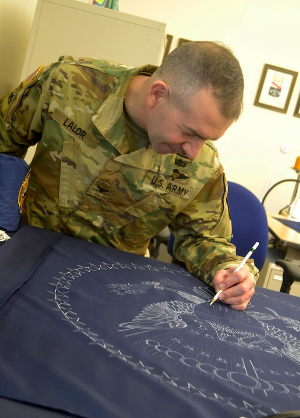 Army Col. Michael Lalor, Army Medical Logistics Command commander, signs the presidential flag during a visit to the Flag Room at DLA Troop Support Jan. 7, 2020 in Philadelphia.