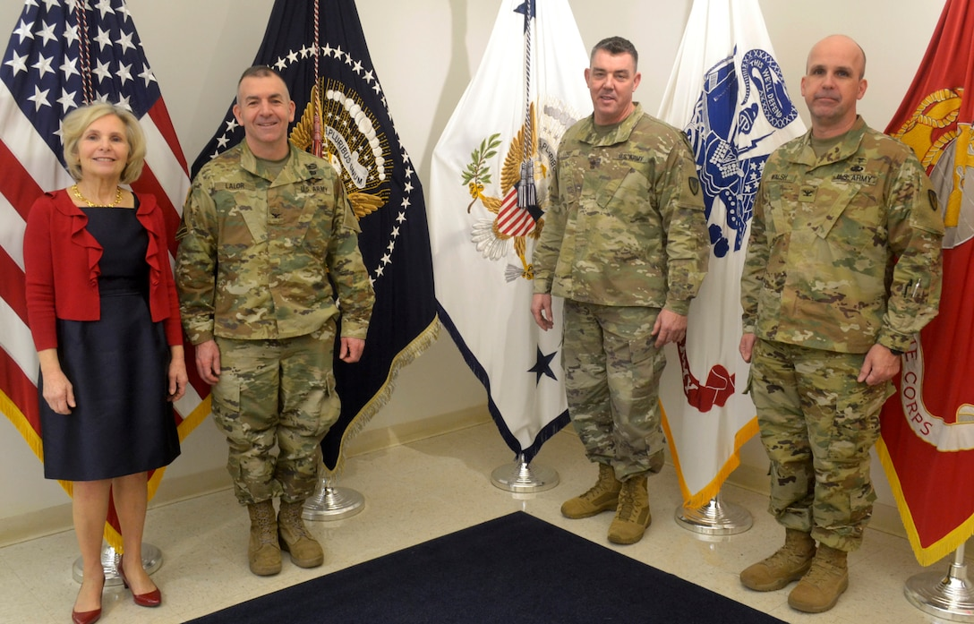 Army Col. Michael Lalor, Army Medical Logistics Command commander, left center, Sgt. Maj. Corey Lord, AMLC sergeant major, right center, and Col. Timothy Walsh, AMLC deputy commander, right, pose for a photo with Linda Farrell, DLA Troop Support Flag Room supervisor, at DLA Troop Support Jan. 7, 2020 in Philadelphia.