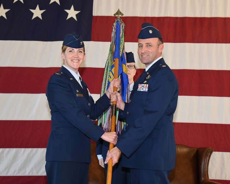 Col. Samantha Weeks, 14th Flying Training Wing commander, passes the 14th Operations Group guidon to Lt. Col. William McElhinney as he assumes command of the 14th OG Jan. 6, 2020, on Columbus Air Force Base, Miss. McElhinney is the former commander of the 43rd Flying Training Squadron, which administers and executes the Air Education and Training Command/Air Force Reserve Command Associate Instructor Pilot Program and provides Active, Guard, Reserve and Traditional Reserve IPs to augment the cadre of active-duty pilots conducting pilot training. (U.S. Air Force photo by Elizabeth Owens)