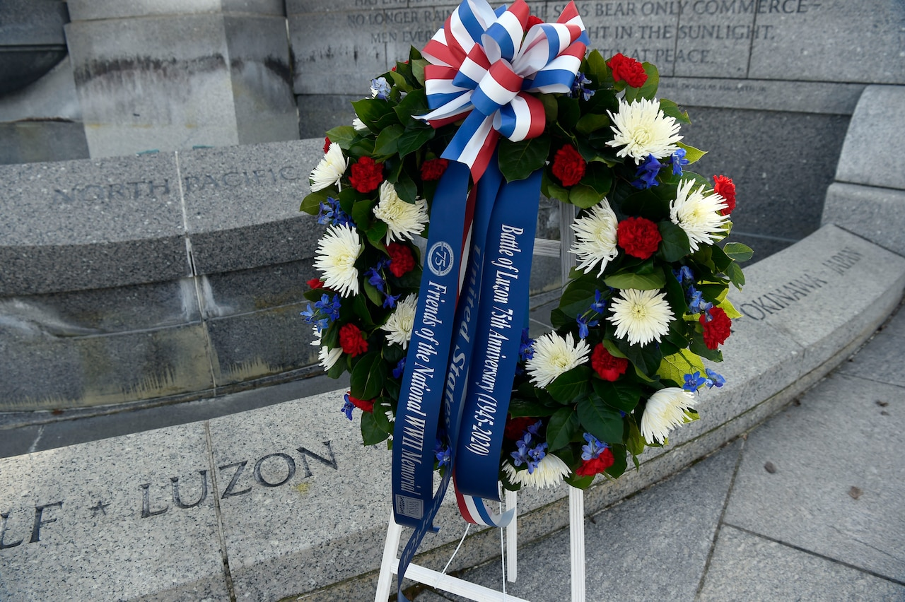 "A floral wreath adorned with banners that read ""Battle of Luzon 75th Anniversary,"" ""United States,"" and ""Friends of the National WWII Memorial"" sits in front of a stone memorial that reads ""Luzon."""