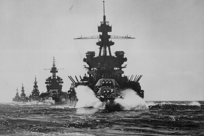 A line of large military ships with guns pointed in the air moves through the ocean.