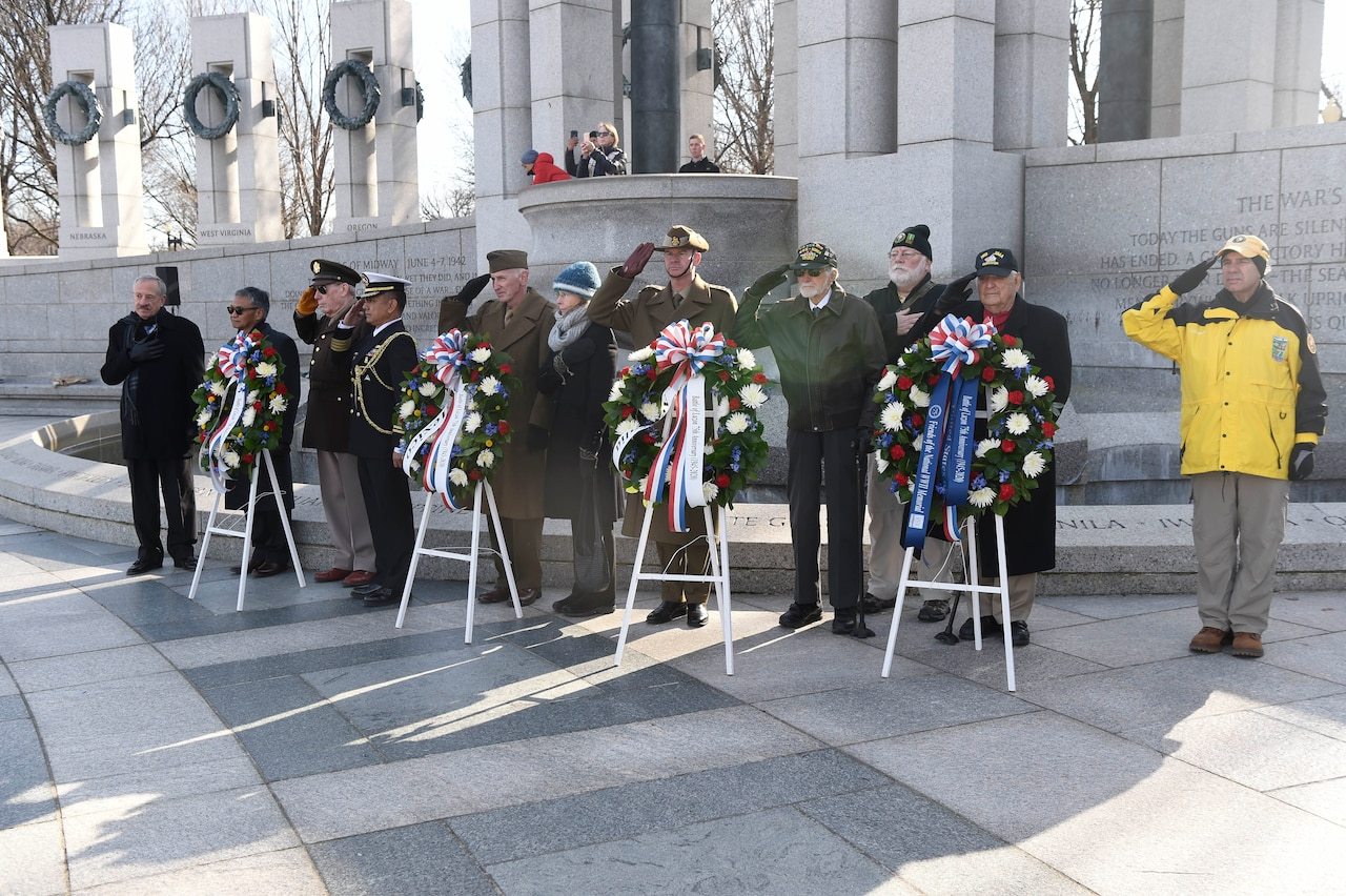 Eleven people stand near a military memorial and behind four floral wreaths. Many are saluting.