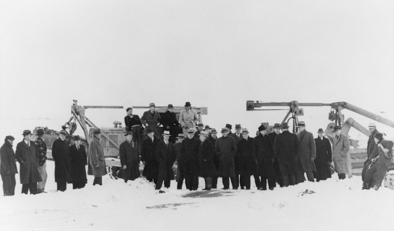 A black and white photo of several base and community officials gathering during the ground breaking of Hill Field on a snowy day Jan. 12, 1940.