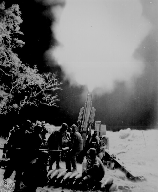 Soldiers fire a large gun at night.