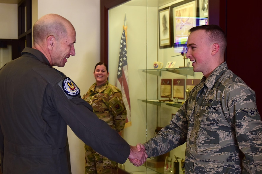 General Mike Holmes, Commander of Air Combat Command, shakes hands with an Airmen who has excelled within his squadron.