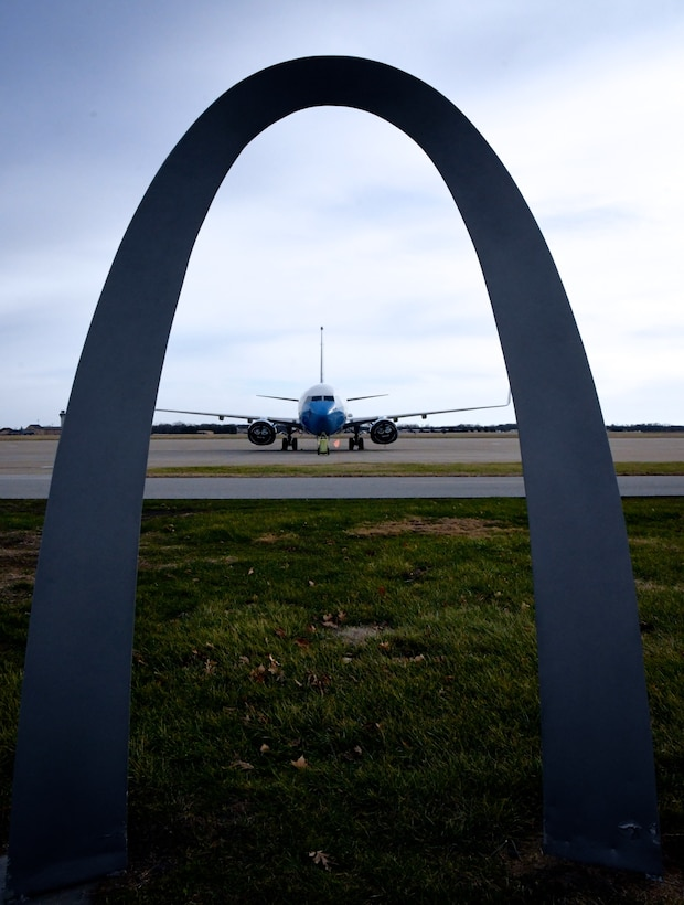 """An Air Force Reserve Command C-40C aircraft sits ready for another mission, framed by a replica of the Gateway Arch at Scott Air Force Base, Ill..  The 932nd Airlift Wing's Maintenance Group is responsible for training Airmen to inspect, maintain and repair Air Force Reserve Command C-40C planes. The 932nd MXG's management enables the 932nd Operations Group's pilots to fly distinguished visitor (DV) airlift around the world, anywhere they are needed by the nation's leaders. Here, several maintainers prepare to make inspection checks on the plane on a windy winter day, January 2, 2020 at Scott Air Force Base, Ill. The Illinois unit, which is part of 22nd Air Force, under Air Force Reserve Command, flies four of the C-40C planes worldwide. The unit is known as the """"Gateway Wing"""" among Air Force Reserve units.  (U.S. Air Force photo by Lt. Col. Stan Paregien)"""