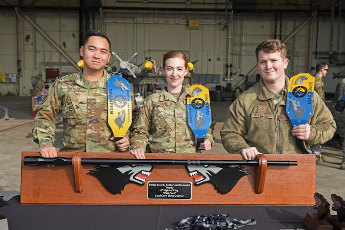 Representing the 80th Aircraft Maintenance Unit, U.S. Air Force Senior Airman Calvin Corpuz, left, Staff Sgt. Kailin Rime, center, and Senior Airman John Whitaker, right, took home the trophy for load crew of the quarter during the 8th Maintenance Group's fourth quarter Weapons Load Crew Competition at Kunsan Air Base, Republic of Korea, Jan. 3, 2020. The three-person crews were evaluated on safety, reliability, technical proficiency and time. (U.S. Air Force photo by Staff Sgt. Mackenzie Mendez)