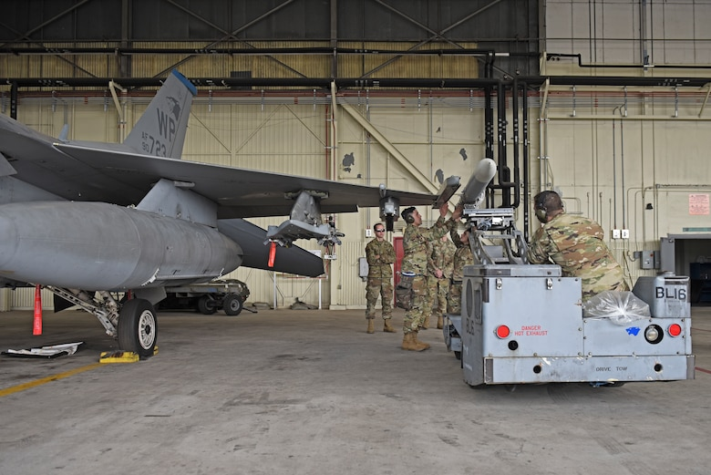A 35th Aircraft Maintenance Unit load crew team loads an F-16 Fighting Falcon aircraft during the 8th Maintenance Group's fourth quarter Weapons Load Crew Competition at Kunsan Air Base, Republic of Korea, Jan. 3, 2020. Prior to the competition, the crews were graded on a weapons system knowledge exam, a tool kit inspection and dress and appearance. (U.S. Air Force photo by Staff Sgt. Mackenzie Mendez)
