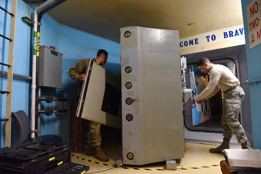 Airman 1st Class and Senior Airman perform maintenance on a launch control center blast door