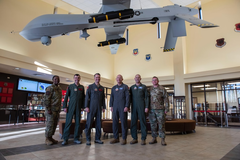 Air Combat Command leadership stand with 432nd Wing Leadership for a group photo under an MQ-1 Predator.