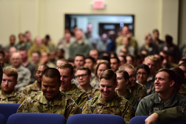 Airmen laugh in a crowd at an all-call.