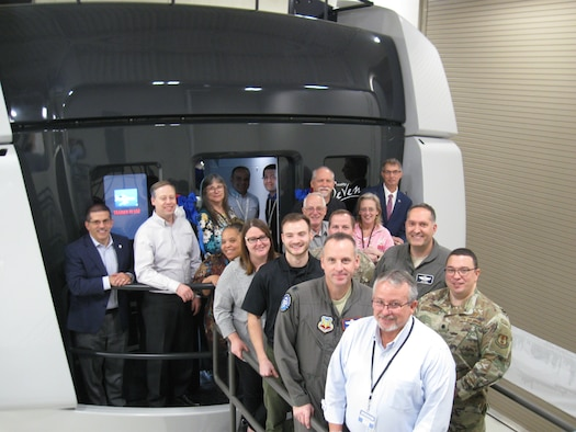 Members of the Simulators Division and 552nd Air Control Group pose in front of the first delivery of the DRAGON Flight Training Device at Tinker Air Force Base, Okla., in December 2019. (Courtesy photo)