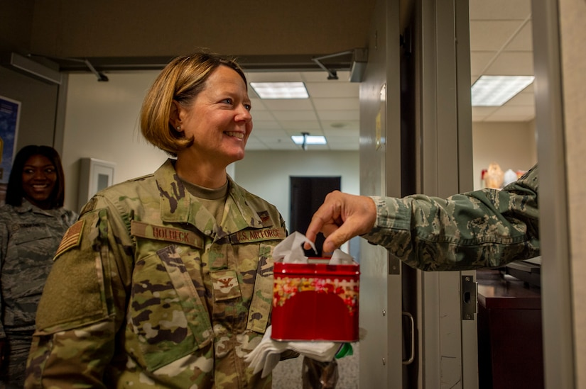 Picture shows Col. Amy Holbeck handing out small boxes of treats to Airmen.