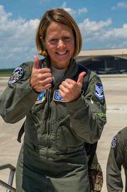 Picture shows Col. Holbeck holding two thumbs up before boarding and E-8C JSTARS aircraft.
