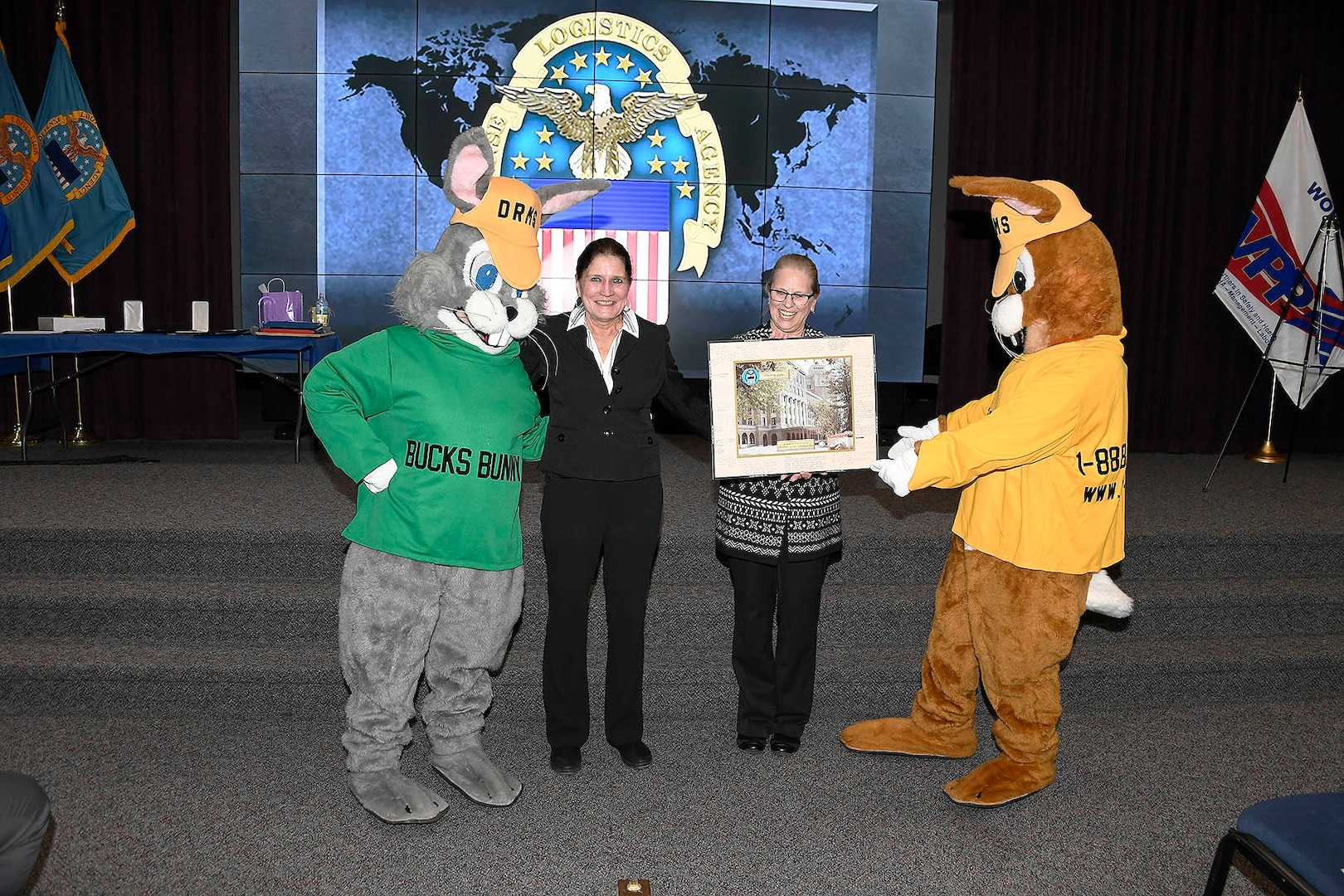 Mascots stand with Sherry Low and lady holding a picture