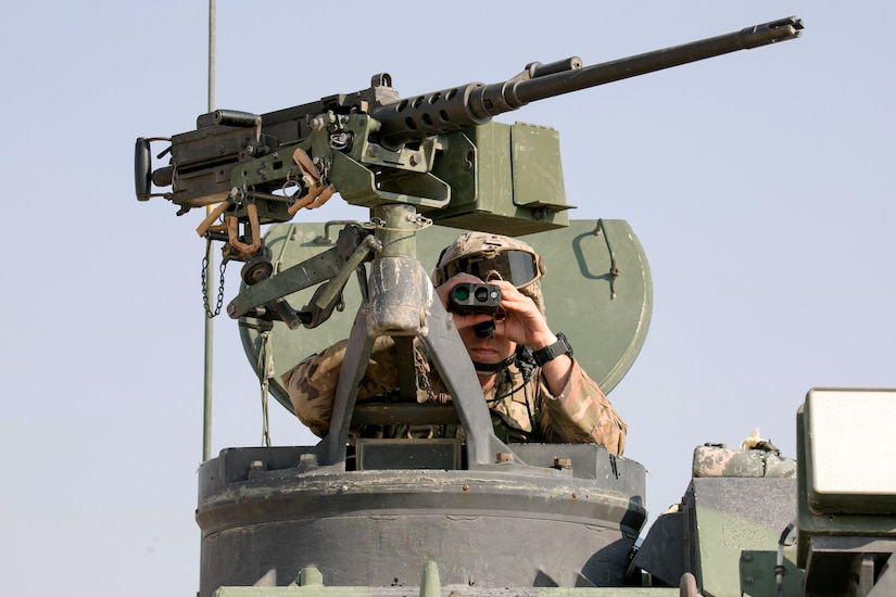 A soldier looks through binoculars.